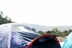 Camper dans une tente sur le dessus de la montagne Photographie stock libre de droits