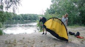 Camper, die herauf das Zelt, vorbereitend zu Nacht in den wilden, grünen Tourismus sich setzen und wandern Glückliches Reisekonze stock video footage