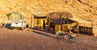 Camper en Afrique avec la carlingue en bois d'abri dans le lever de soleil de désert Photographie stock libre de droits