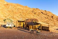 Camper en Afrique avec la carlingue en bois d'abri dans le lever de soleil de désert Photographie stock