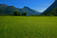Camper and grass field. Camper on a large grass field in the mountains Royalty Free Stock Photo