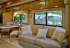 Camper interior. Elegant camper interior with chairs and sofa, camp site seen through the windows Stock Photography