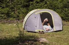Camper looking at the clock. Camper lying in tent and looking at the clock Royalty Free Stock Images