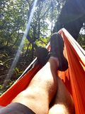 Camper relaxing in hammock. A camper relaxing in a travel hammock between trees in the sunlight Stock Images