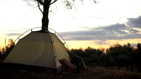 Camper resting in tent early in picturesque place, overnight in wild, sunrise. Stock photo stock photos