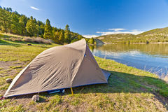 Camper's Tent on a Mountain Lake. A camper's tent sits by the shore of a mountain Lake Stock Images