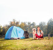 Camper sitting on grass and hugging a dog Stock Photography