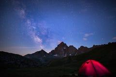 Camper sous le ciel étoilé et manière laiteuse à la haute altitude sur les Alpes Tente lumineuse dans le premier plan et la crête Images libres de droits