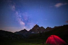 Camper sous le ciel étoilé et manière laiteuse à la haute altitude sur les Alpes Tente lumineuse dans le premier plan et la crête Photo libre de droits