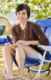 Camper text messaging on cell phone Stock Images