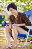 Camper text messaging on phone Stock Photo