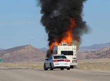 Camper in trouble. Camper caught on fire on side of road Stock Photo