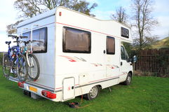 Camper van. Side view of a camper van with bikes on a rack at the back parked on a camp site pitch in the countryside Royalty Free Stock Photography