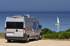 Camper van on the beach. Camper van and sailing boat on the beach of Scivu, Sardinia, Italy Royalty Free Stock Photography