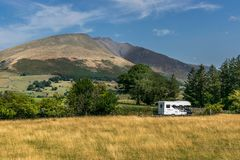 A camper van or motor home next to a mountain. royalty free stock images