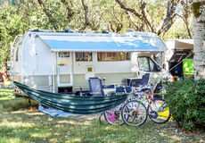 Camper van on parking in camping not far from Trieste, Italy. Mobile motor home RV (caravan) with chairs, bicycles and hammock in nature landscape. Vacation royalty free stock photos