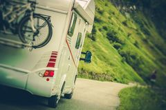Camper Van on the Road. Class C Motorhome Coach with Bikes on the Rear Side Bike Rack. Family RV Travel Stock Photo