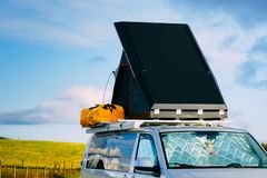 Camper van with tent on roof on roadside royalty free stock photos