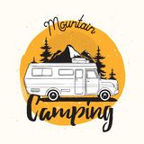 Camper van, travel trailer or recreational vehicle driving on road against mounts and forest on background and mountain. Camping lettering handwritten with Royalty Free Stock Photography