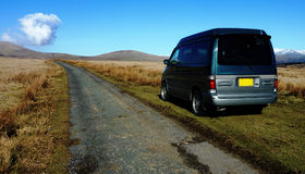 Camper van in wilderness. A Bongo camper van is parked next to a lonely narrow road. Unusual cloud formation in the background Royalty Free Stock Photography