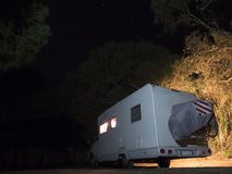Camper in the woods at night under starry sky Stock Images