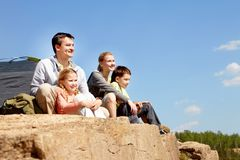 Campers on cliff. Portrait of family of travelers sitting on rocky cliff Royalty Free Stock Photo