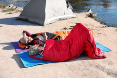Campers lying in sleeping bags. On wild beach stock photos