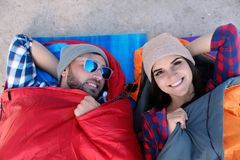 Campers lying in sleeping bags on sand. Top view royalty free stock photos