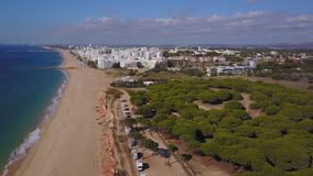 Campers in pine trees on red cliffs by beautiful wide beaches of Quarteira, Algarve, Portugal stock video