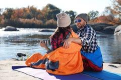 Campers sitting in sleeping bags. On wild beach stock image