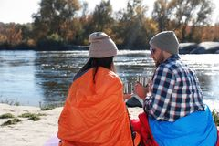 Campers sitting in sleeping bags. On wild beach royalty free stock photography