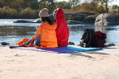 Campers sitting in sleeping bags. On wild beach royalty free stock images