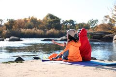 Campers sitting in sleeping bags on wild beach. Space for text royalty free stock image