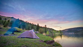Campers Tent at Sunset. A camper's tent is pitched by the shore of a mountain lake as the clouds light up for sunset Stock Photos