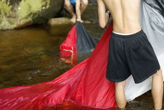 Campers washing tent in river Royalty Free Stock Photo
