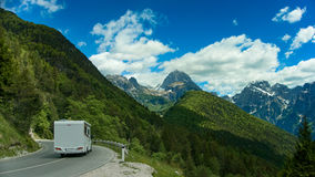 Campervan crossing Passo del Predil with stunning view. Royalty Free Stock Photography