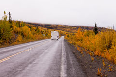 Campervan driving autumn fall highway Yukon Canada. Camper van drives on highway with autumn or fall colorful yellow foliage of boreal forest taiga of yukon Royalty Free Stock Images