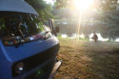 Campervan and Girl. Next to Lake in Dreamy Evening Sun, France royalty free stock photography
