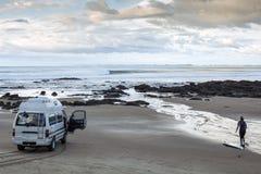 Campervan y persona que practica surf Imagenes de archivo