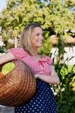 Campesina feliz con una cesta con las zanahorias en su jardín Foto de archivo
