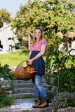 Campesina feliz con una cesta con los carrotts Fotografía de archivo