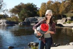 Campeur femelle avec le sac de couchage près de l'étang images stock