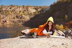 Campeur femelle dans le livre de lecture de sac de couchage dehors photos stock