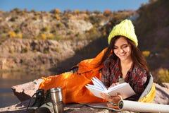 Campeur femelle dans le livre de lecture de sac de couchage dehors image libre de droits