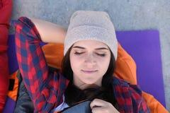 Campeur femelle se situant dans le sac de couchage sur le tapis images stock