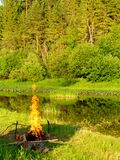 Campfire 1. A fire burning on a river shore in the evening Stock Photos