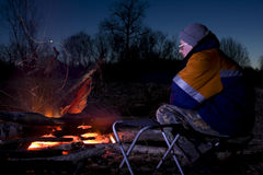 By the Campfire. A man sits by a blazing, evening campfire royalty free stock photography