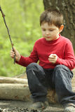 At campfire. Boy in red with thin stick sitting on log at campfire Stock Photo