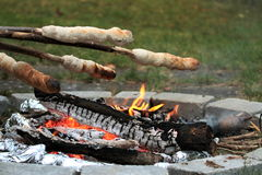 Campfire and bread baking with stick Stock Images