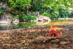 Campfire burning on stony river bank in Caucasus mountain forest. Scenic summer sunny day landscape. Hiking and picnic leisure act Stock Photo